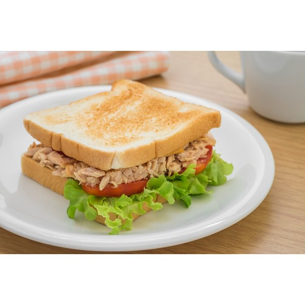 A tuna sandwich with lettuce and tomato on a plate.