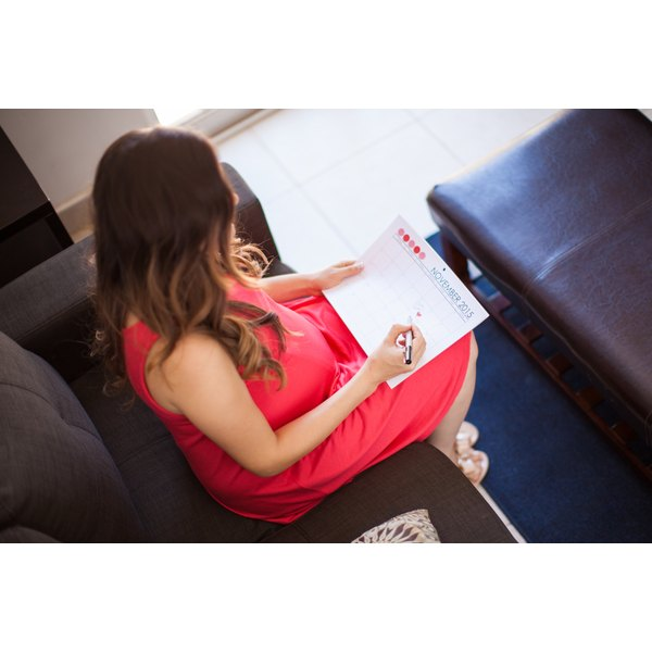 A pregnant woman marking on a calendar in her lap.