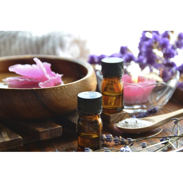 Two bottles of essential oil on a table with herbs and flowers.