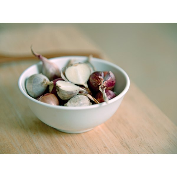 A bowl of garlic cloves on a wooden table.