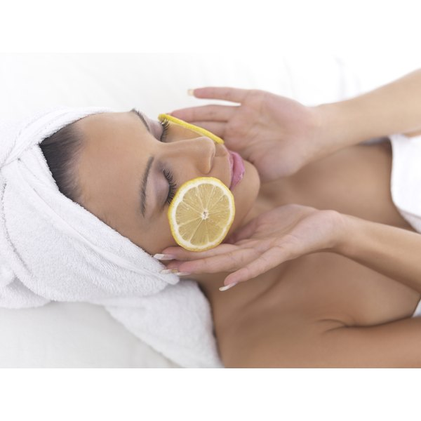 A woman relaxing with lemon slices on her face.