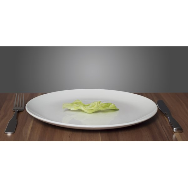 A plate with one small piece of lettuce on it.