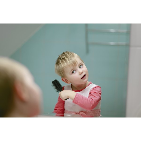 A toddler combing his hair in the mirror.
