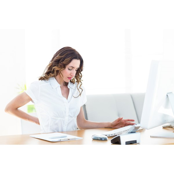 A woman is sitting at her desk with lower back pain.