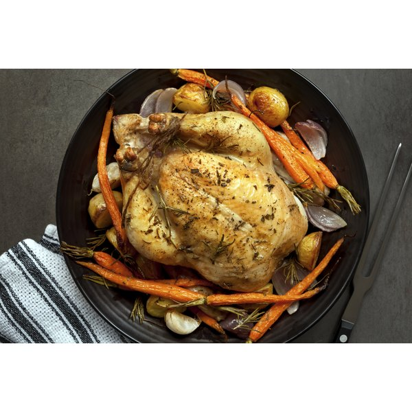 A whole baked chicken sits on a serving plate atop a table.