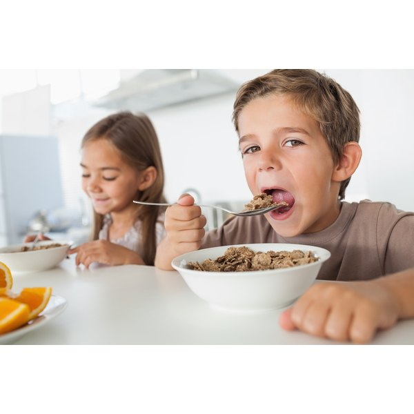 Boy and girl eating bowls of cereal