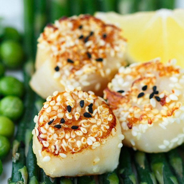 Seared scallops with sesame seeds served over asparagus.