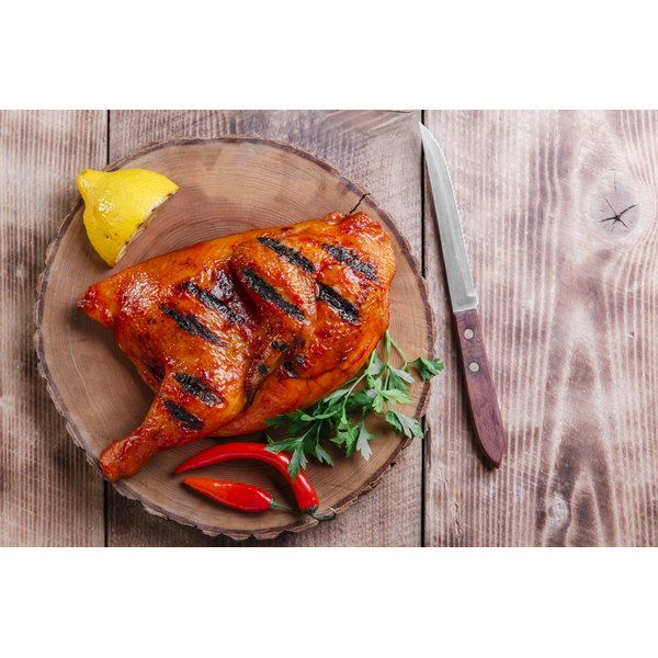 A grilled half chicken with peppers, lemon and garnish.