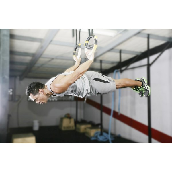 A muscular man is hanging from gym rings.