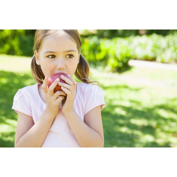 A young girl is biting into an apple.
