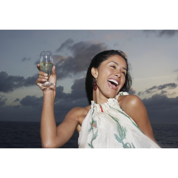 A young woman laughs as she holds up a glass of white wine on an early summer evening.