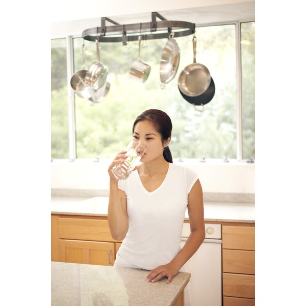 young woman drinking large glass of water in her kitchen