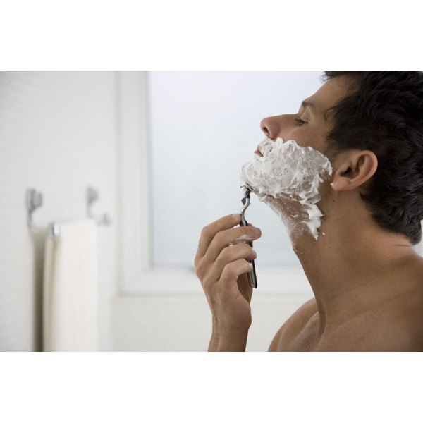 Young man shaving his chin in a mirror.
