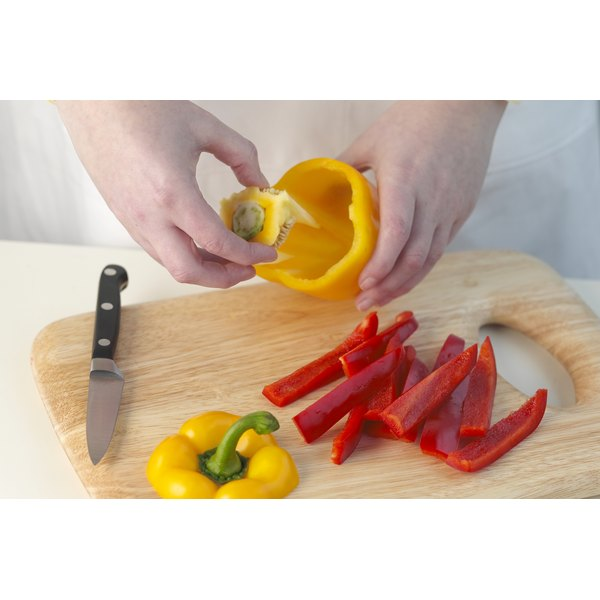 person slicing red and yellow pepper on cutting board in kitchen