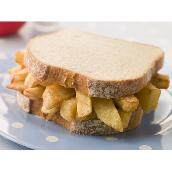 A sandwich made with white bread and British-style fries.