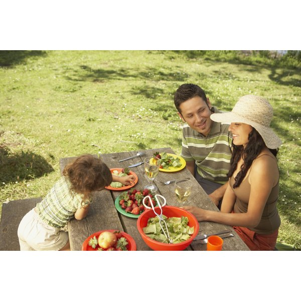 A family is dining outside at a picnic table.