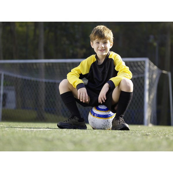 A young soccer player is sitting on a soccer ball on a field.
