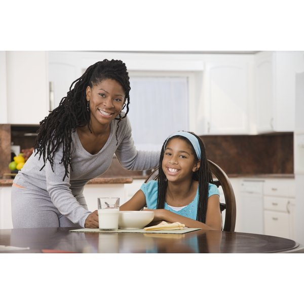 A mother and her daughter at the breakfast table with a glas of milk and a bowl of cereal.