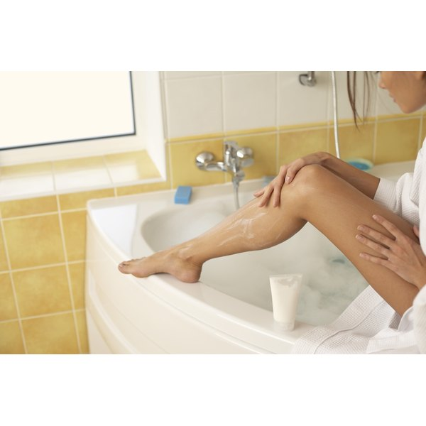 A woman shaves her legs in the bathroom.