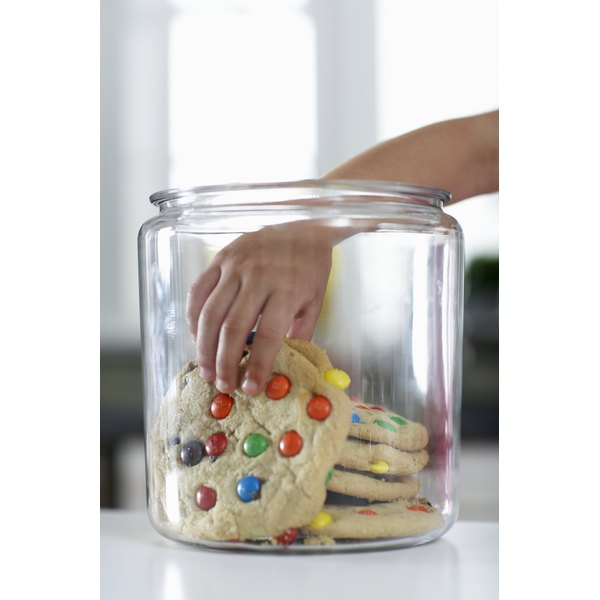 Child's hand stealing a cookie from the cookie jar.