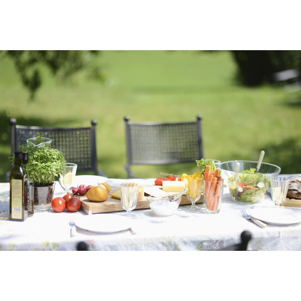An outdoor table is set and healthy vegetables are on the plates.