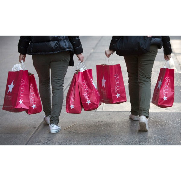 Women carry Macy's store bags full of purchases