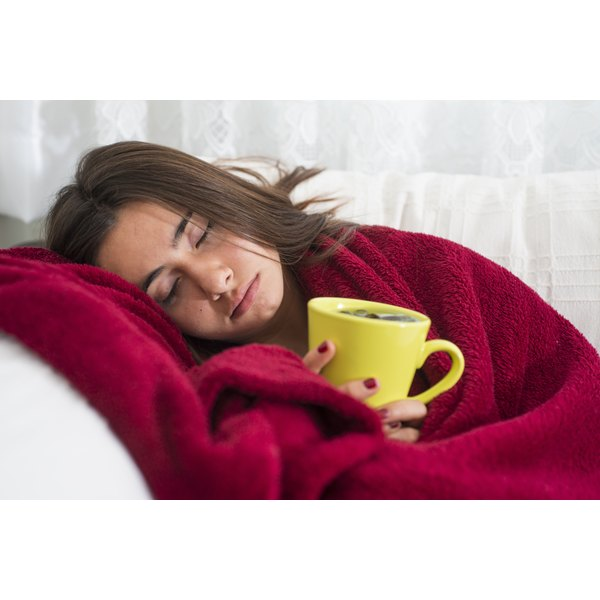 A teenage girl with flu-like symptoms holding a cup of tea.