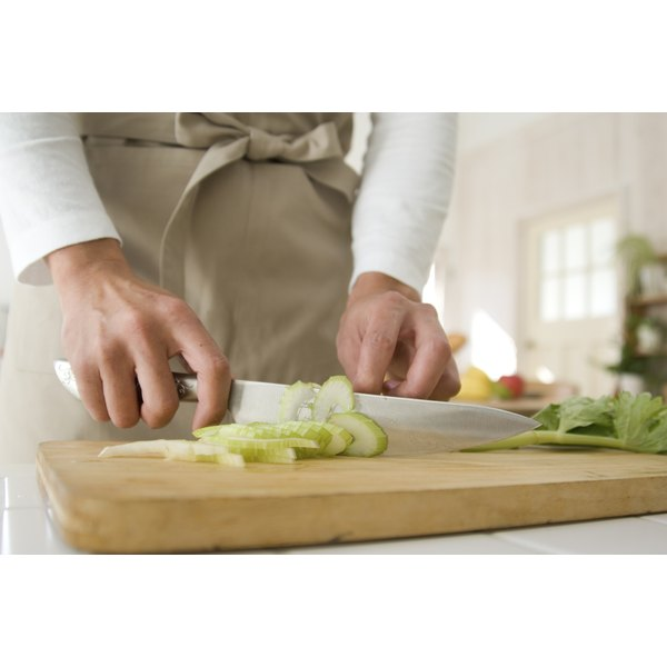 Close-up of a woman slicing celery.