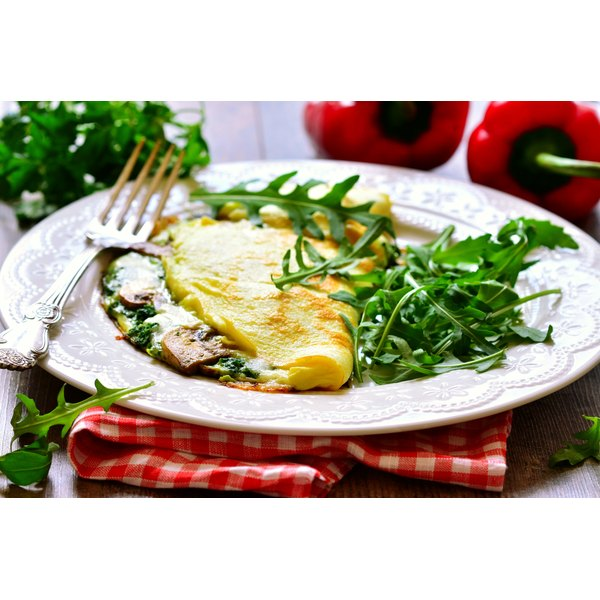 A spinach and mushroom omelette on a plate with fresh arugula.