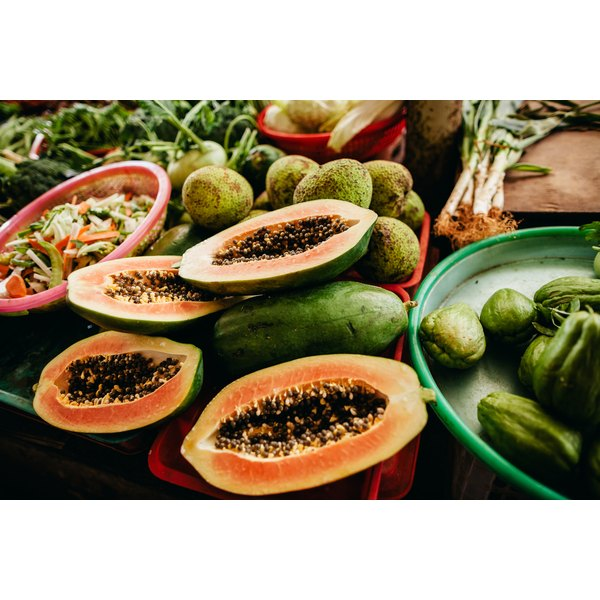 Cut papayas on a table with tropical fruits.
