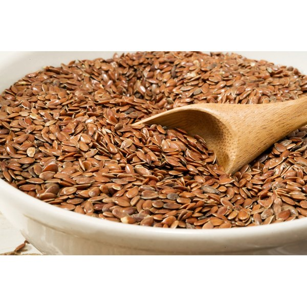 A bowl of flax seeds with a wooden spoon.