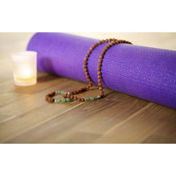 Mala beads on a yoga mat beside a lit candle in a studio.