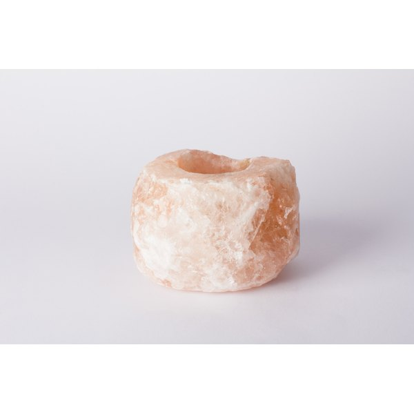 A Himalayan salt candle holder on a white counter.