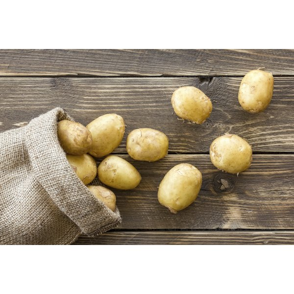 A bunch of poatoes spilling out of a sack.
