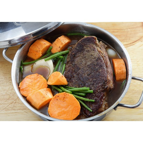 A pot roast cooked with vegetables in a braising pan.