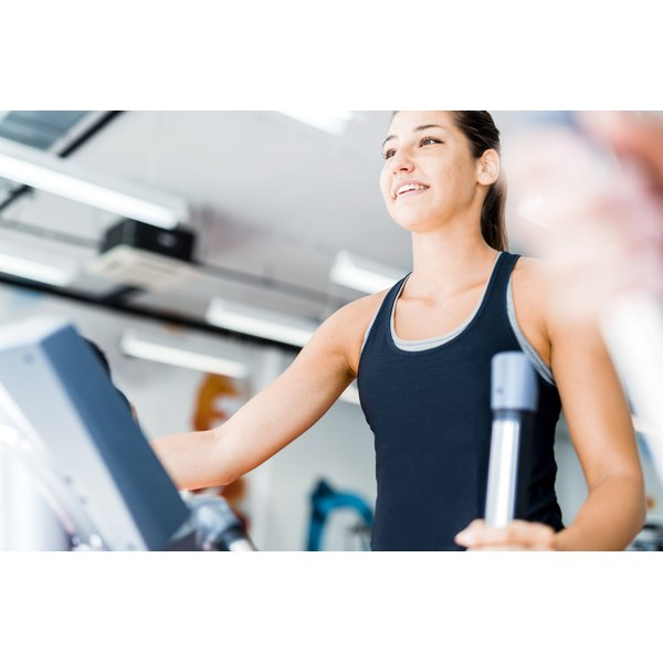 A young woman is exercising on an elliptical machine.