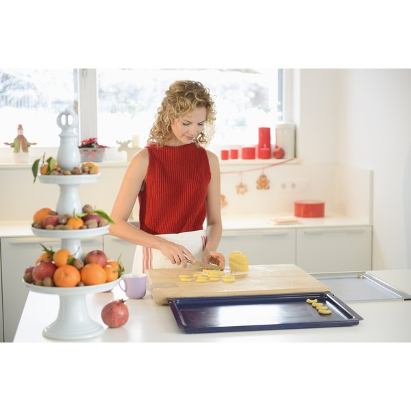 A woman is slicing food in her kitchen.