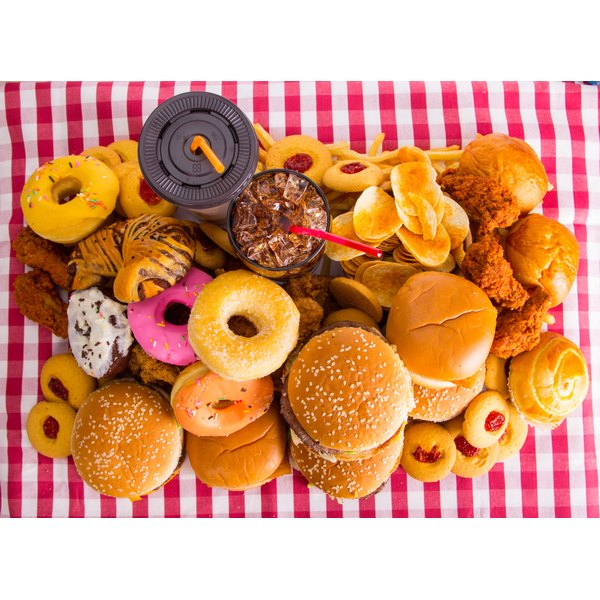 An assortment of unhealthy foods and drinks on a tablecloth.