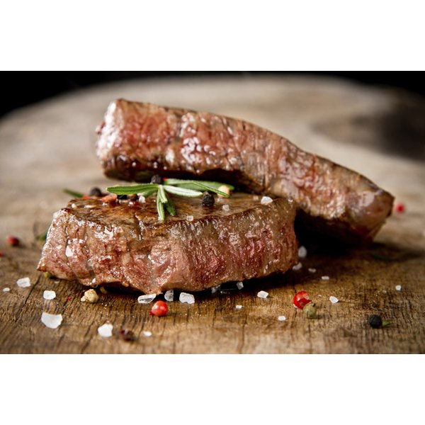 Grilled steaks on a wooden cutting board.