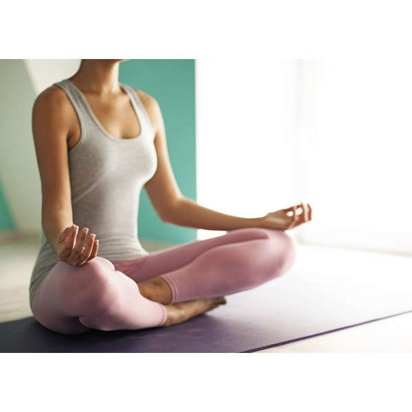 A woman sitting with a straight spine on a yoga mat.