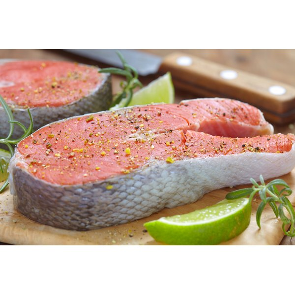 An uncooked salmon steak with salt and pepper.