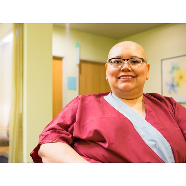 Woman with bald head in medical gown awaiting treatment
