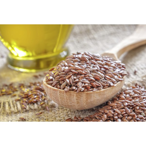 A spoonful of flax seeds and a bottle of oil.