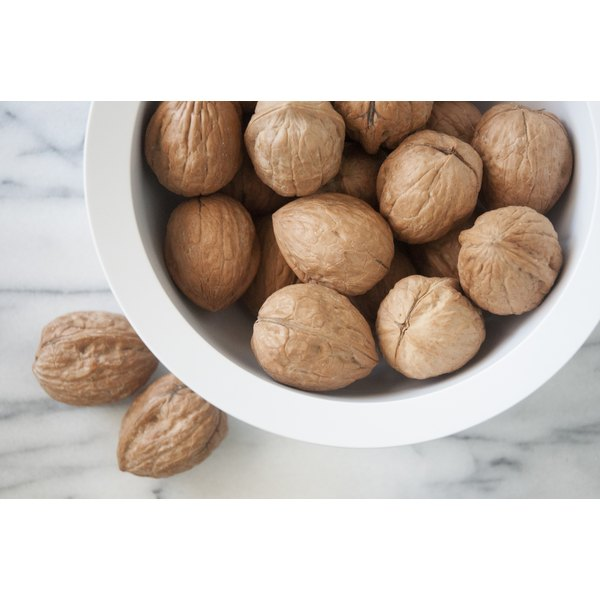 A bowl of walnuts on a marble counter.