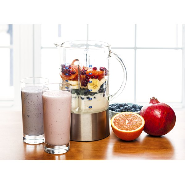 A blender with fruits in it next to two glasses of smoothies and fruit.