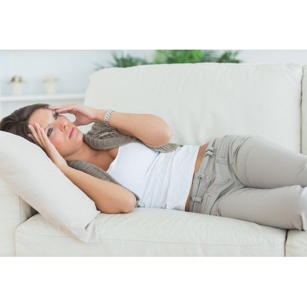 A woman is experiencing a headache and lays back on the couch.