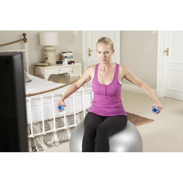 A woman is exercising to a workout DVD.