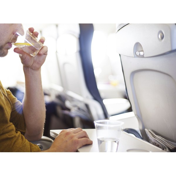 A man is drinking water on an airplane.