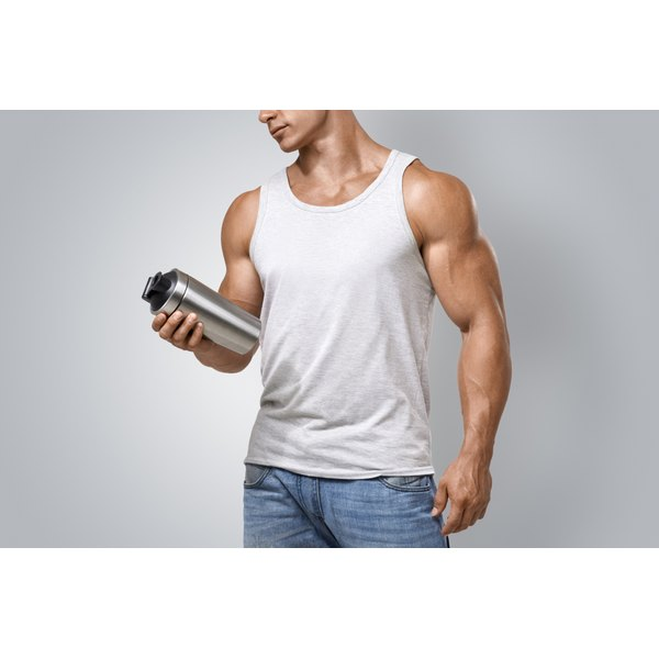 A man is holding a protein shaker.