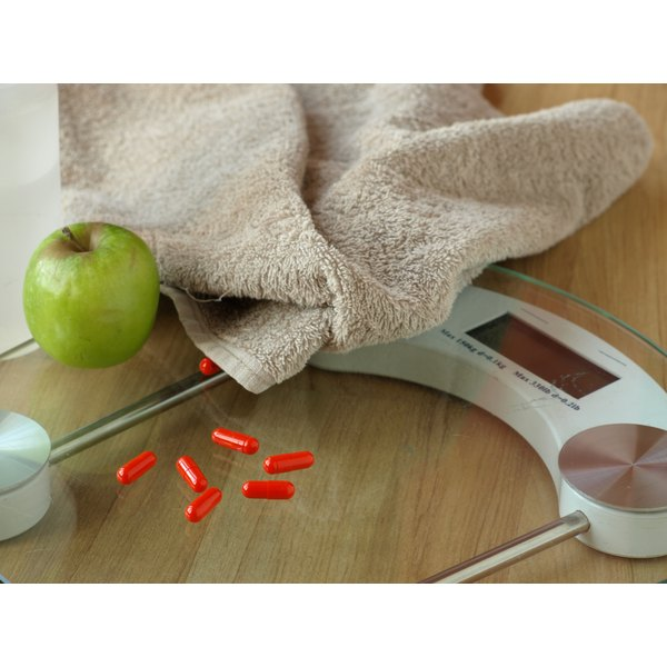 Weight-loss vitamins on a glass bathroom scale with an apple and a towel.